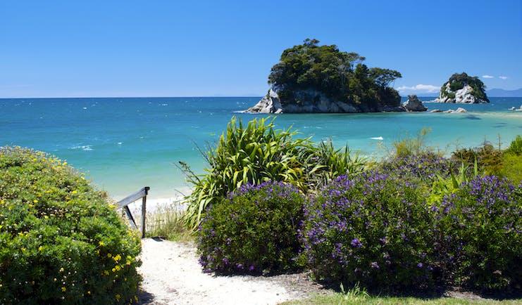Little Kaiteriteri Beach in Abel Tasman National Park, sand, shrubbery, sea, Torlesse Rock in background
