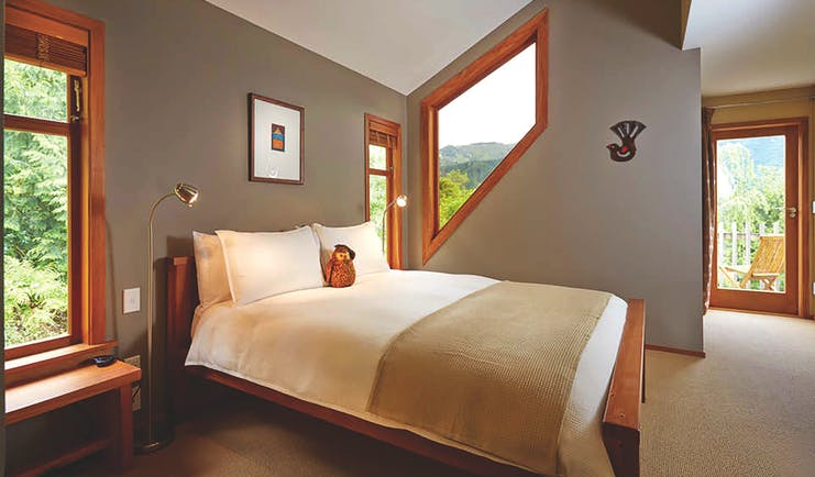 The Resurgence ecoLodge Nelson Abel and Tasman bedroom with angled window and patio door to balcony terrace