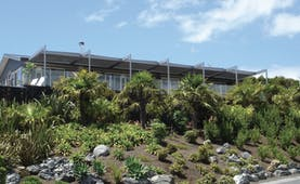 Eagles Nest Northland exterior two storied glass building with beige curved roof surrounded by green plants and trees