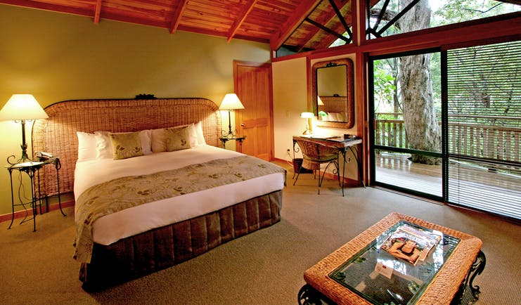Grand Mercure Puka Park Northlands and Bay of Islands bedroom with wicker head board and balcony with tree