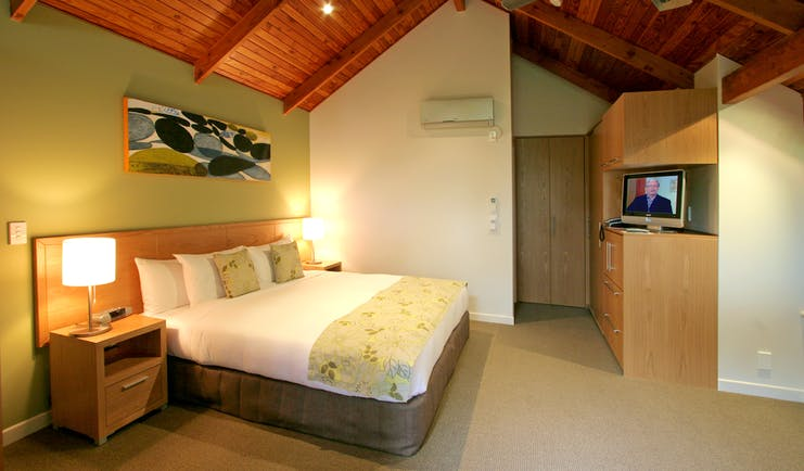 Grand Mercure Puka Park Northlands and Bay of Islands loft bedroom with sofa and balcony with tree