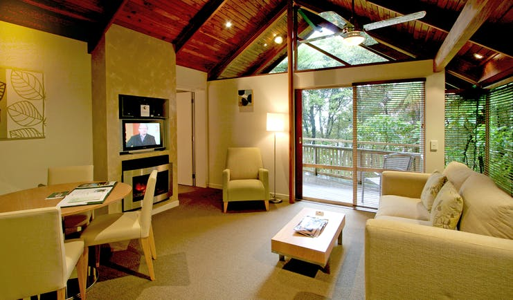 Grand Mercure Puka Park Northlands and Bay of Islands suite lounge area with sofa and fireplace with balcony