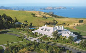 Aerial shot of Kauri Cliffs, hotel building, lawns, sea and coastline