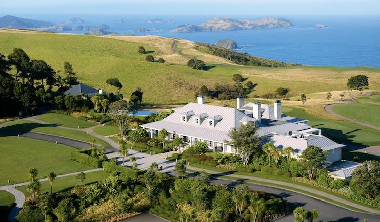 Aerial shot of Kauri Cliffs, hotel building, lawns, sea and coastline