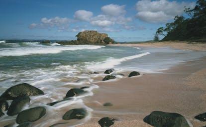 Kauri Cliffs beach, pink sand, blue sea, rocks