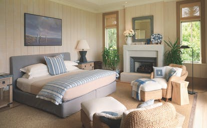 Kauri Cliffs master bedroom, cosy pastel decor, bed, armchairs