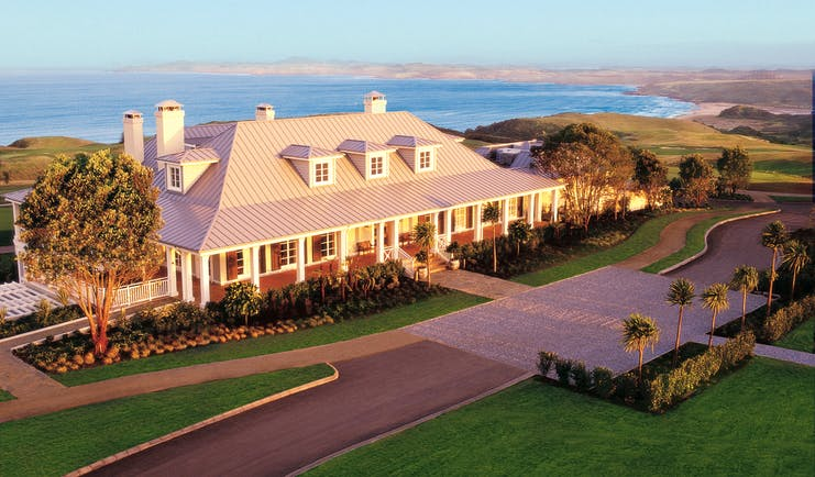Exterior shot of Kauri Cliffs, hotel building, lawns, sea in backgroubnd