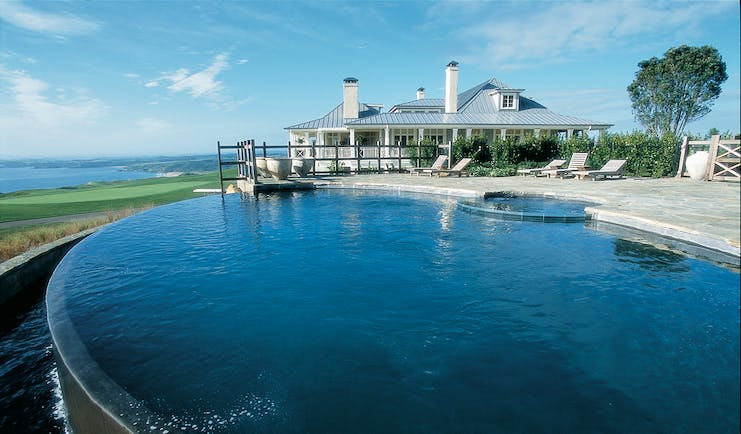 Kauri Cliffs infinity pool, decking, lodge in background, overlooking the sea
