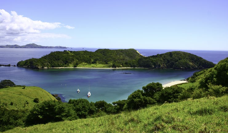 Lonely Bay in the Bay of Islands, verdant greenery, islands, blue seas, boat on water