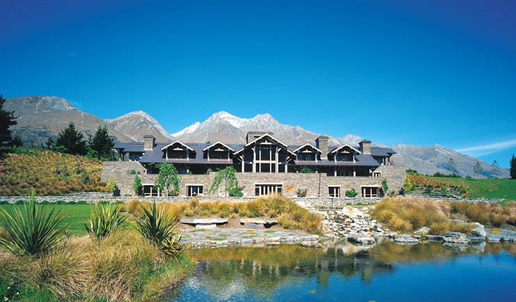 Blanket Bay Otago and Fiordland exterior stone lodge overlooked by snow capped mountain next to lake