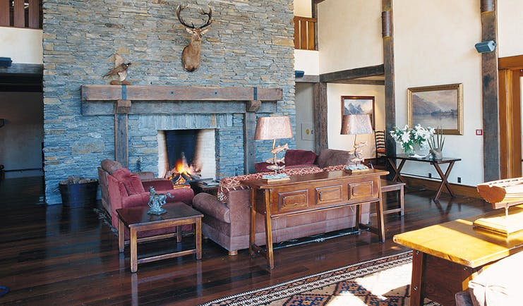 Blanket Bay Otago and Fiordland lounge with sofas and stone fireplace with taxidermy deer head