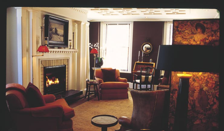 Lounge area ath Eichardt's with a fire place and armchairs around the room