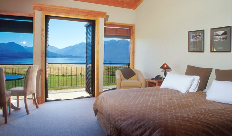 Bedroom with large double bed and doors opening onto a balcony over looking mountains