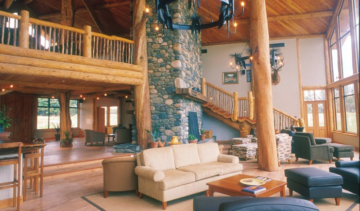 Fiordland Lodge lounge with wooden ceiling and floor, with wooden staircase leading upstairs and sofas