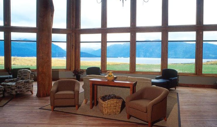 Fiordland Lodge sitting area with wooden floors, armchairs and wood pannelled windows looking over mountains