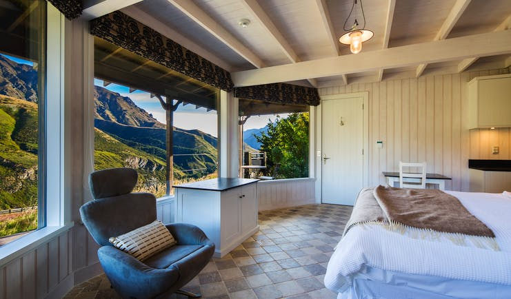 Mahu Whenua Otago and Fiordland cottage bedroom with armchair and panoramic windows with mountain view