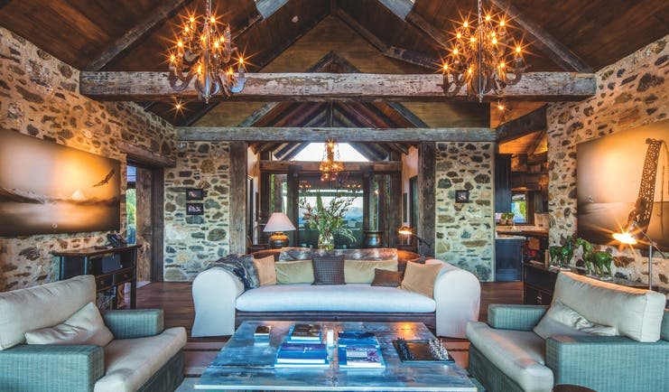 Mahu Whenua Otago and Fiordland living room with exposed stone and beams and chandeliers