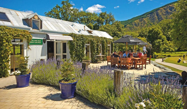 Millbrook Lodge Otago and Fiordland outdoor dining corrugated metal building with outdoor seating area and lavender