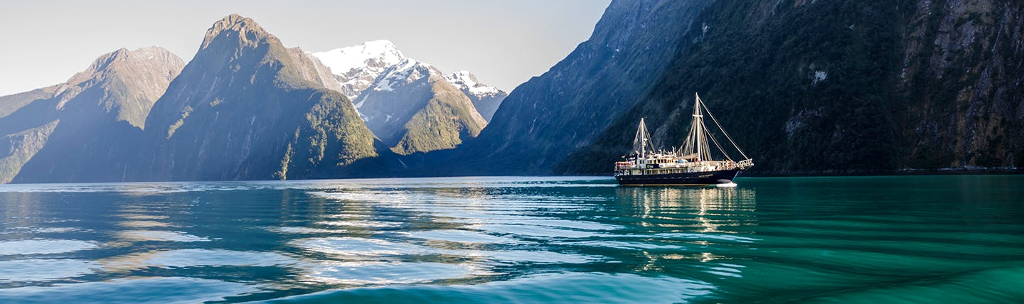 Icy green water with steep grey mountains behind and cruise ship