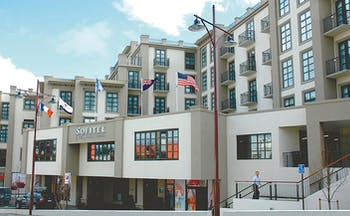 Sofitel Queenstown Otago and Fiordland exterior white and grey building with several flags