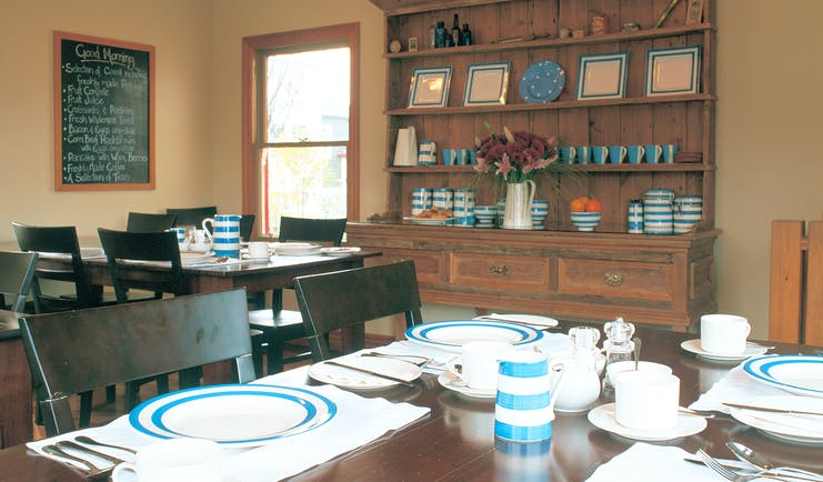 Breakfast dining area with tables and chairs set up and wooden shelves on the wall