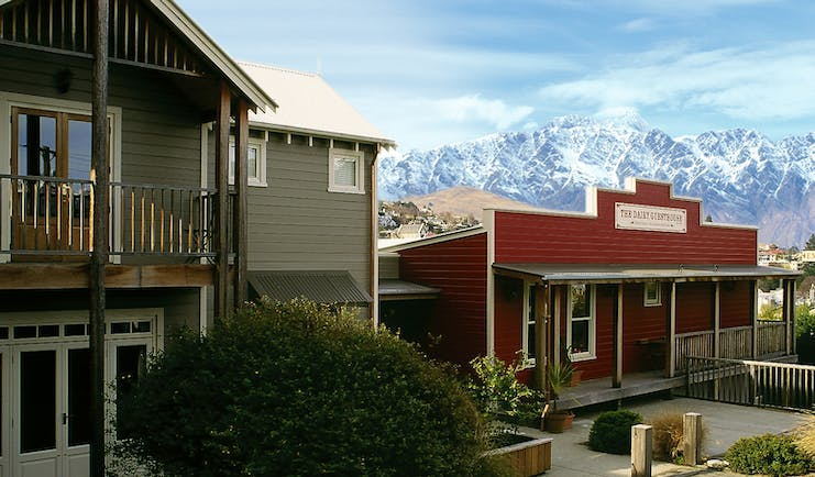 The Dairy Otago and Fiordland exterior red lodge building with snowy mountain in the background