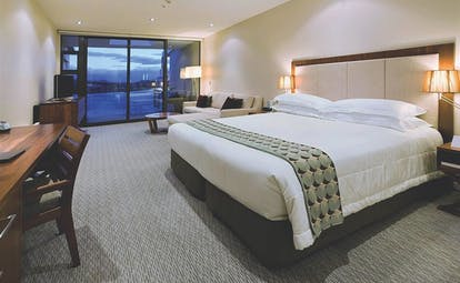 The Rees Hotel Otago and Fiordland bedroom with seating area and large patio door
