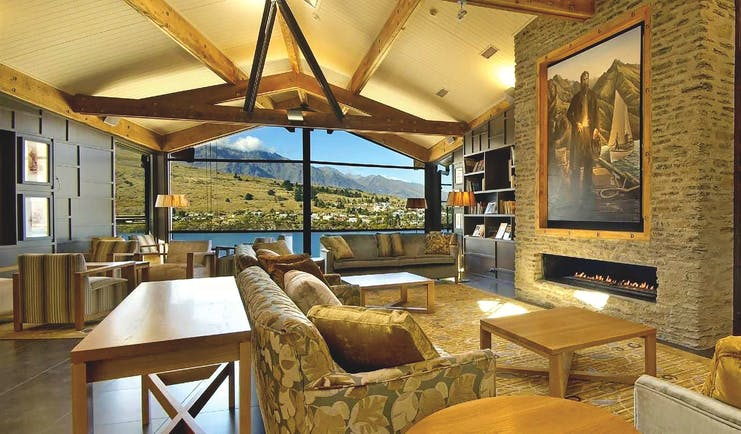 The Rees Hotel Otago and Fiordland lounge area with large painting fireplace and large window