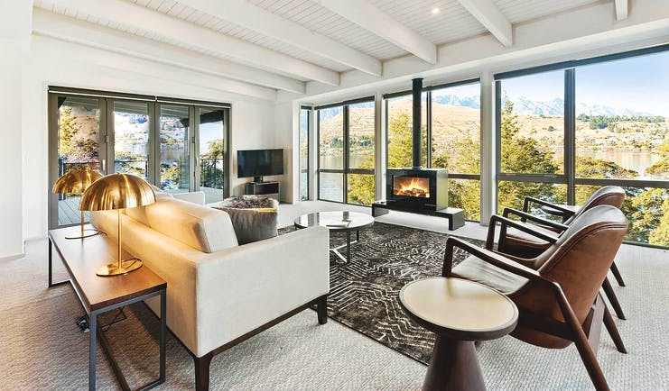 The Rees Hotel Otago and Fiordland suite lounge with sofa and leather armchairs with panoramic view