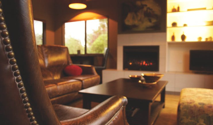 Peppers Parehua Wairarapa sitting room with brown leather chairs and fireplace