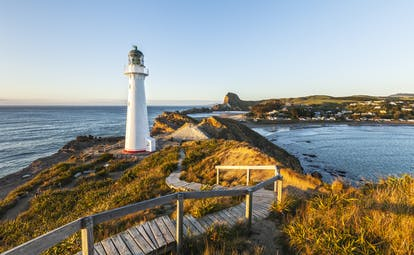 Castlepoint Lighthouse in Wairarapa, rugged headland, sea, sunset