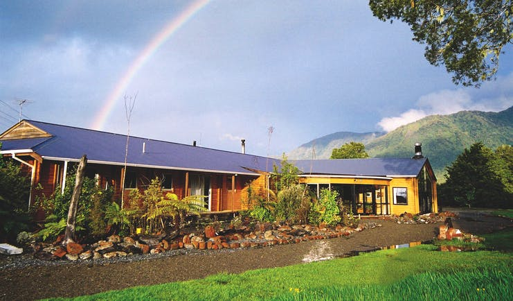 Exterior shot of Westwood Country House, lush lawn, lodge, rainbow in the sky