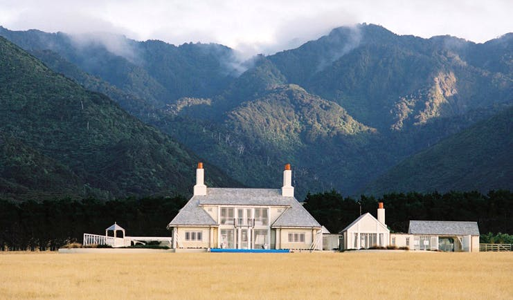 Wharekauhau Lodge Wairarapa lodge mountain exterior view of lodge complex in front of wooded mountains