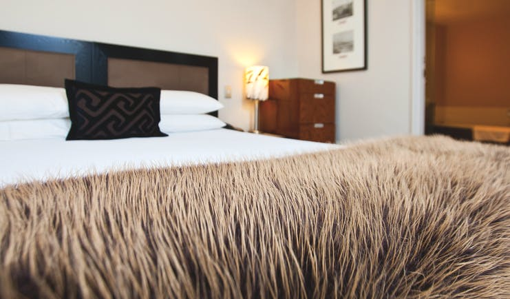 Bolton Hotel Wellington bedroom with faux fur blanket and view to bathroom