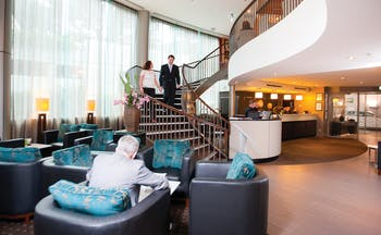Bolton Hotel Wellington lobby couple walking down stairs to lobby with seating area