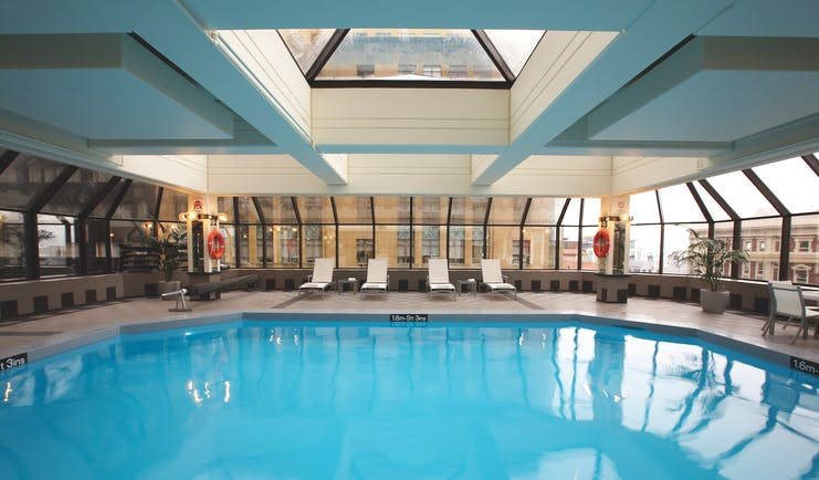 The Intercontinental Wellington indoor pool with panoramic windows city view and loungers