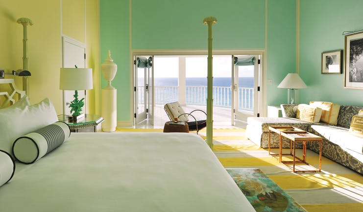 Malliouhana premium room with pastel colours, large double bed and sofa, with balcony with sea views