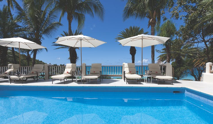 Blue Waters Antigua adults only pool sun loungers and umbrellas