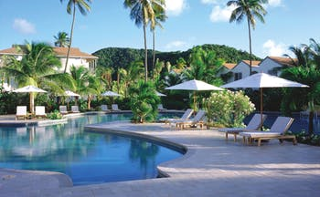 Carlisle Bay Antigua pool palm trees and sun loungers
