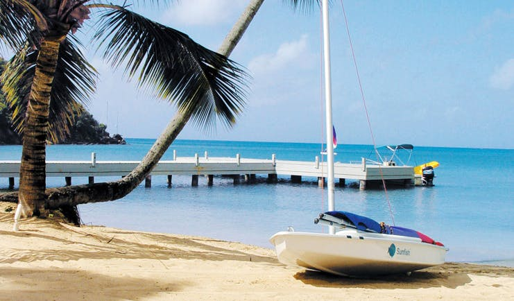 Carlisle Bay Antigua water sports boat on sand jetty beach ocean palm tree