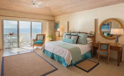 Curtain Bluff Antigua cliff suite bedroom with balcony overlooking the ocean