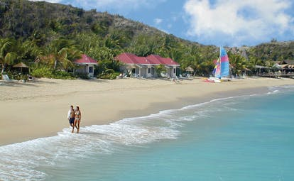 Galley Bay Antigua couple walking on beach san clear blue water boats