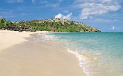 Galley Bay Antigua shore clear blue waves lapping sandy beach
