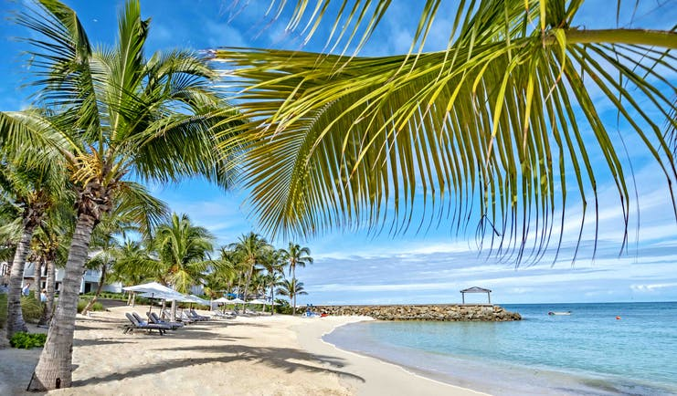 Hodges Bay Resort beach, golden sands, palm trees, turquoise waters