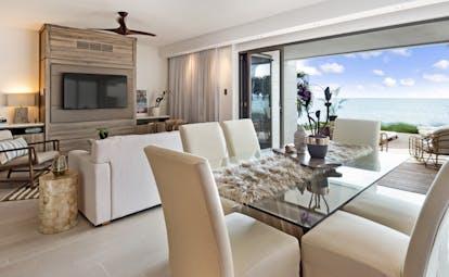 Dining room of villa at Hodges Bay Resort, bright modern decor, view of sea