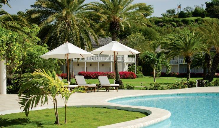 Inn at English Harbour Antigua Poolside sun loungers umbrellas palm trees
