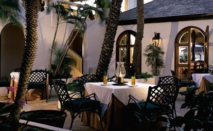 Jumby Bay Antigua outdoor dining area tables chairs palm trees