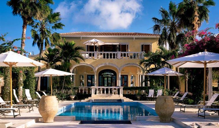 Jumby Bay Antigua pool sun loungers umbrellas hotel building in background