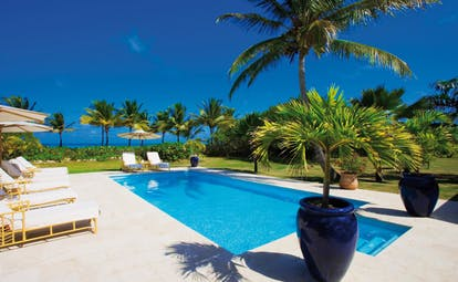 Jumby Bay Antigua tir na nog pool private pool sun loungers umbrellas palm trees