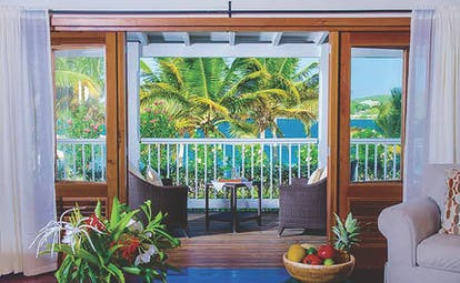 Nonsuch Bay Antigua premium beach suite lounge leading to balcony and outdoor seating overlooking beach